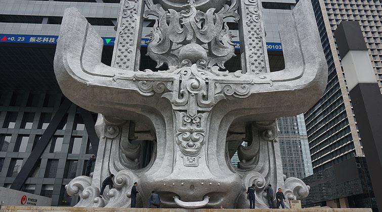 中央第七巡视组在对深圳证券交易所党委进行为期近两个月的巡视后,这组价值9000万的巨型雕塑去留成了很大的难题。这组9000万的雕塑《龙盈乾坤》为清华大学教授、福娃之父韩美林所创,高48米,采用白铜材质。  主雕塑以牛头为基础,两条蛟龙腾空而起,组成庄重遒劲的龙门,顶部是羽翼飞扬的凤凰在昂首盘旋。这是目前全球最高的白铜雕塑。  副雕塑群由高11.